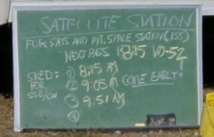 The chalkboard outside the Satellite Station lists upcoming passes.